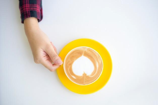 Heiße latte kunst in der gelben tasse auf dem schreibtisch