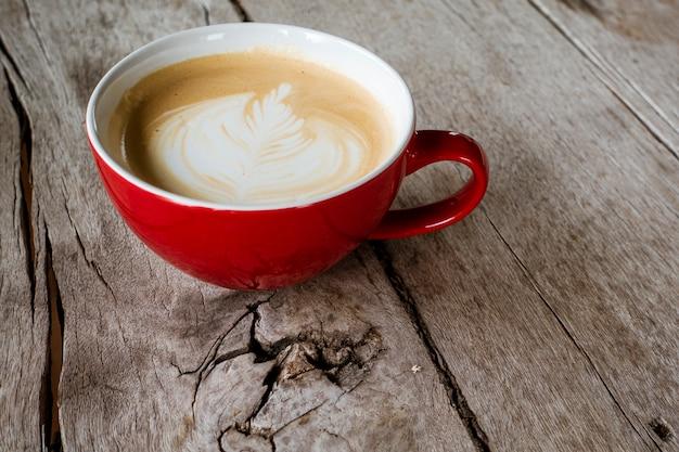 Heiße lattekunst auf hölzernem schreibtisch