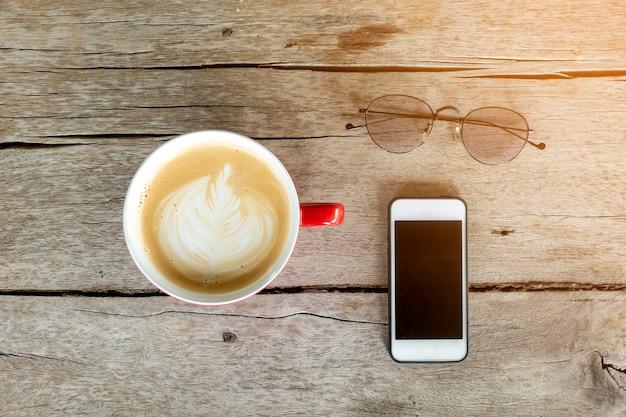 Heiße lattekunst mit intelligentem telefon auf holz