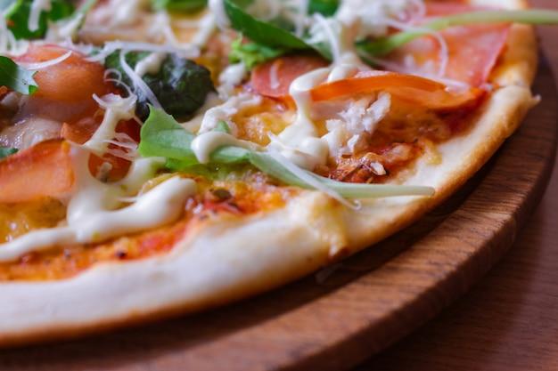 Heiße leckere pizza mit rucola, tomaten und speck