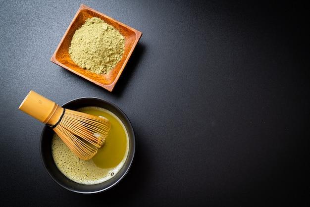 Heiße matcha-grüntee-tasse mit grüntee-pulver und bambus-schneebesen