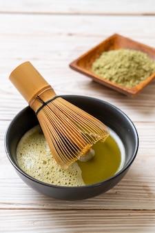 Heiße matcha-grüntee-tasse mit grüntee-pulver und schneebesen