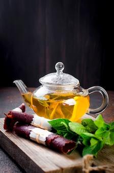 Heiße minze tee in einer teekanne und trockenen früchten lederrolle
