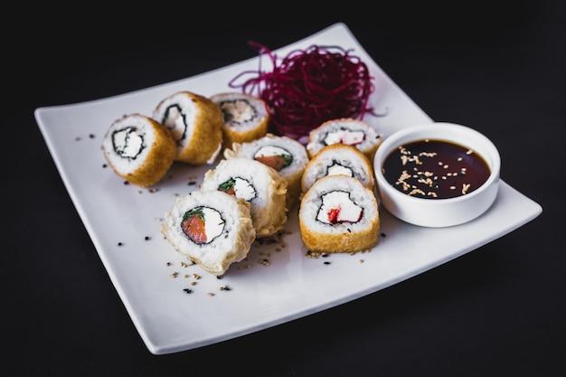 Heiße panko-sushi-rolle mit sojasauce und sesam