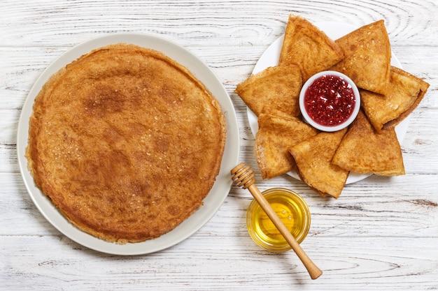 Heiße pfannkuchen mit ahornsirup und himbeermarmelade. das gute du frühstück. ansicht von oben