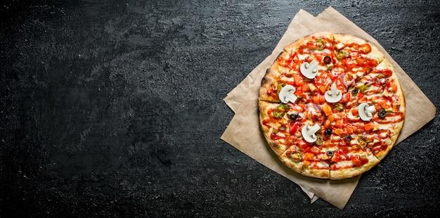 Heiße pizza auf papier. auf rustikal