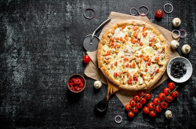 Heiße pizza auf papier mit kirschtomaten auf dunklem holztisch