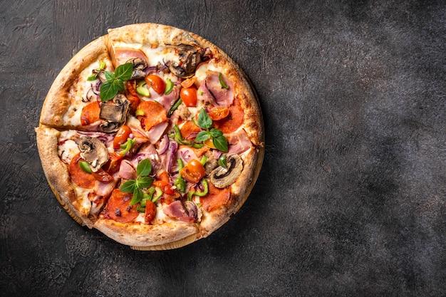 Heiße pizza mit peperoni-mozzarella-pilzen und speck auf schwarz