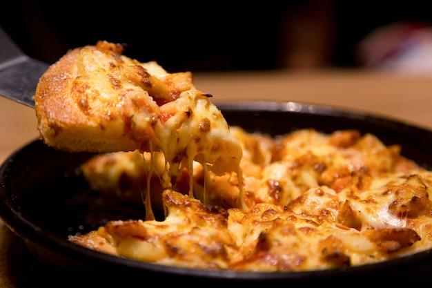 Heiße pizzascheibe mit schmelzendem käse auf einer tabelle