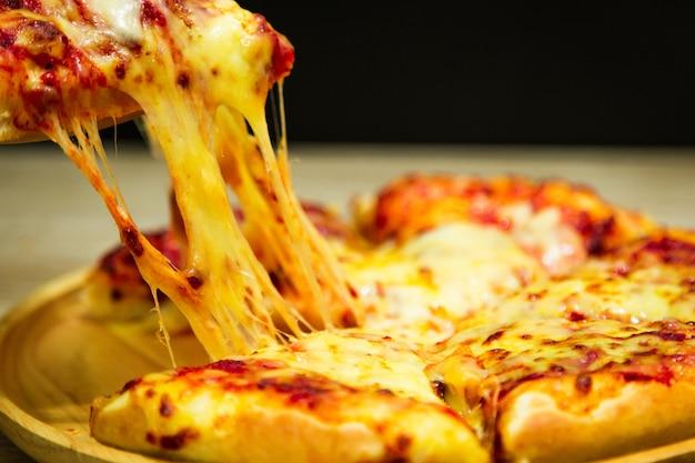 Heiße pizzascheibe mit tropfendem mozzarellakäse.