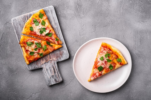 Heiße pizzastücke mit mozzarella-käse-schinken-tomate und petersilie auf hölzernem schneidebrett und plattensteinbetonhintergrund-draufsicht