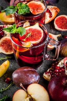Heiße rote fruchtsangria mit äpfeln, pflaumen, feigen, granatapfel und gewürzen