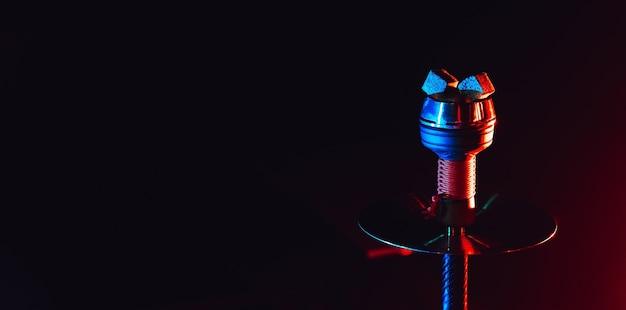 Heiße rote kohlen für shisha shisha in einer keramischen metallschale mit roter blauer neonbeleuchtung auf einem schwarzen hintergrund mit einem kopienraum