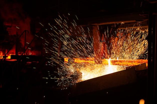 Heiße rote stahlknüppel beim brennerschneiden. hintergrund der schmiede- und metallurgieindustrie.