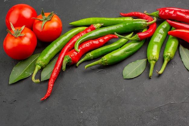 Heiße rote und grüne paprika-rote tomaten-lorbeerblätter der unteren ansicht auf schwarzem hintergrund