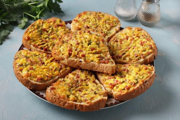 Heiße sandwiches mit käse und wurst in einem teller auf hellblauem hintergrund, horizontalformat, nahaufnahme, selektiver fokus