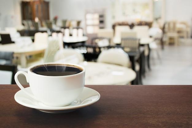 Heiße schale schwarzer kaffee auf tischplatte im café. drinnen.