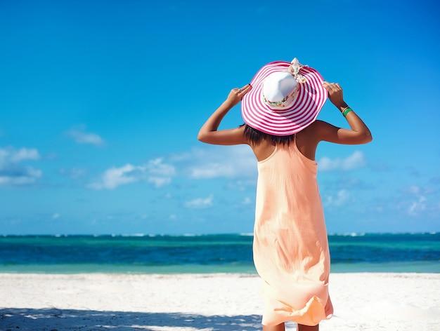 Heiße schöne frau in buntem sonnenhut und kleid, die nahe strandozean am heißen sommertag auf weißem sand gehen