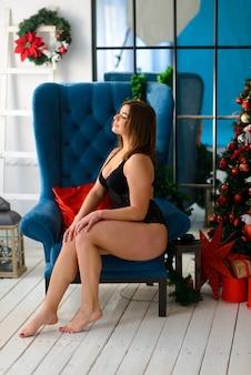 Heiße schöne frau in spitzenschwarzwäsche, die nahe dem kamin aufwirft. weihnachtsinnenraum. sinnliches mädchen.