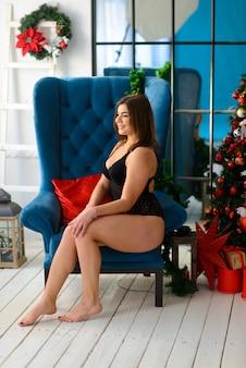 Heiße schöne frau in spitzenschwarzwäsche, die nahe dem kamin aufwirft. weihnachtsinnenraum.