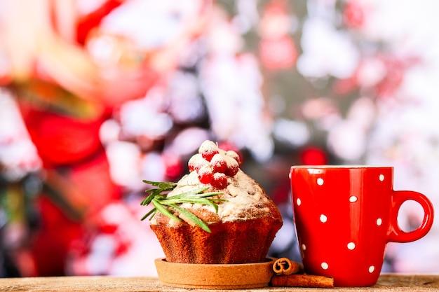 Heiße schokolade auf dem hintergrund eines weihnachtsbaums mit einem weihnachtscupcakesüßigkeiten für das neue jahr