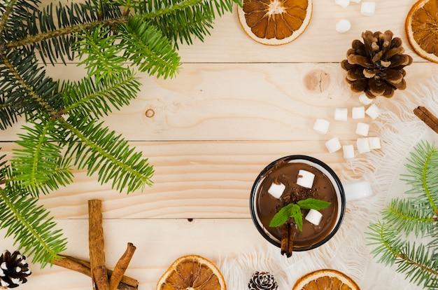 Heiße schokolade auf dem schreibtisch mit marshmallows, orangen und fichtenbeulen
