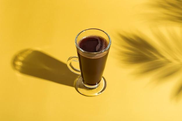 Heiße schokolade auf farbigem hintergrund, im schatten einer palme. konzept des weltschokoladentages. der feiertag der schokolade