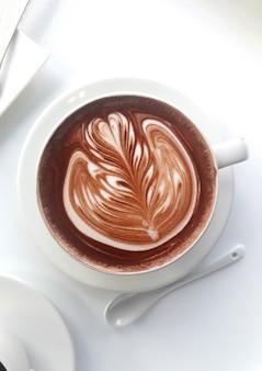 Heiße schokolade im becher auf weißem tisch