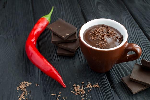Heiße schokolade in der braunen tasse und roter peper chili auf dem schwarzen holz
