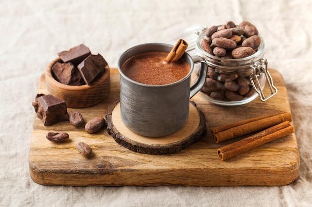Heiße schokolade in einem metallbecher mit einer zimtstange auf dem tischdecken-kopierraum