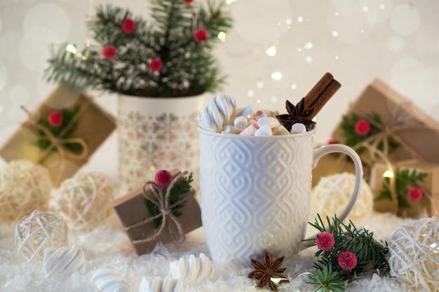 Heiße schokolade in einer weißen tasse mit marshmallows und weihnachtsgeschenken auf dem hellen licht. weihnachtsgetränk.