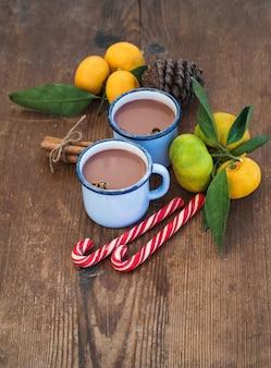 Heiße schokolade in emaille-metallbechern, frischen mandarinen, zimtstangen, tannenzapfen und zuckerstangen