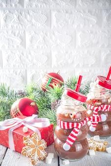 Heiße schokolade in lustigen schneemannflaschen mit marshmallow
