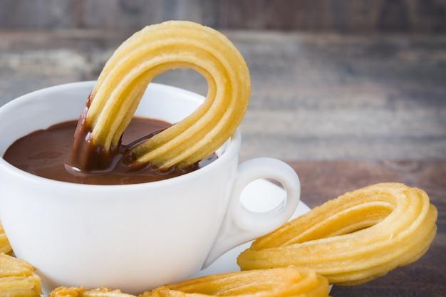 Heiße schokolade mit churros auf spanischem frühstück des holztischs