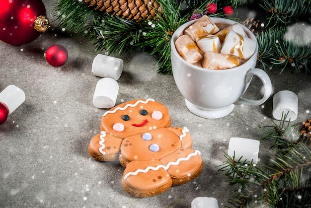 Heiße schokolade mit eibisch, lebkuchenmannplätzchen, tannenbaumasten und weihnachtsdekor