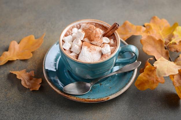 Heiße schokolade mit eibischen und autumn leaves auf stein- oder betonoberfläche