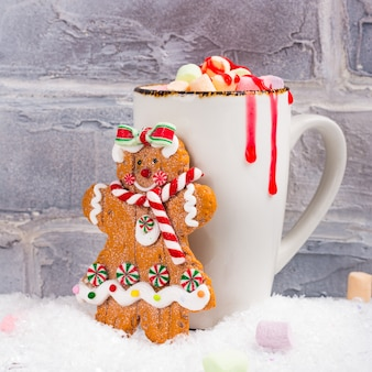 Heiße schokolade mit eibischen und lebkuchenmädchen-plätzchenspielzeug über hintergrund der weißen weihnacht
