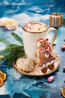Heiße schokolade mit eibischen und plätzchen auf weihnachtshintergrund