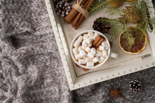 Heiße schokolade mit eibischzimtstangen, anis, nüsse auf hölzernem behälter
