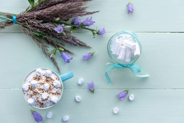 Heiße schokolade mit leckeren marshmallows in einer blauen tasse am frühen morgen.