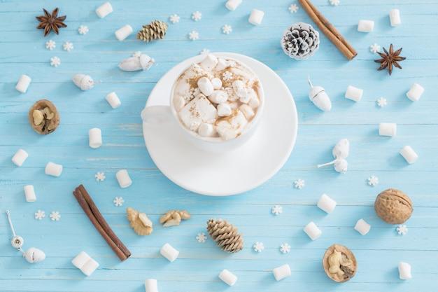 Heiße schokolade mit marshmallow auf blauem holz