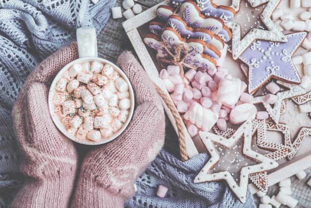 Heiße schokolade mit marshmallow-bonbons und lebkuchenplätzchen weibliche hände in handschuhen, die eine warme kokokasse halten