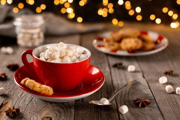 Heiße schokolade mit marshmallow in roter tasse auf holztisch. christams winter-heißgetränk-menürezept