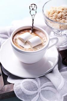 Heiße schokolade mit marshmallows im becher, auf farbigem holzhintergrund