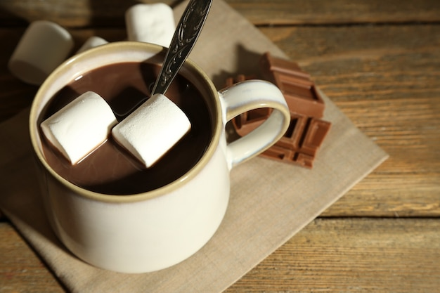 Heiße schokolade mit marshmallows im becher, auf holzoberfläche