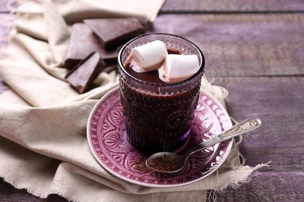 Heiße schokolade mit marshmallows im glas, auf farbigem holztisch