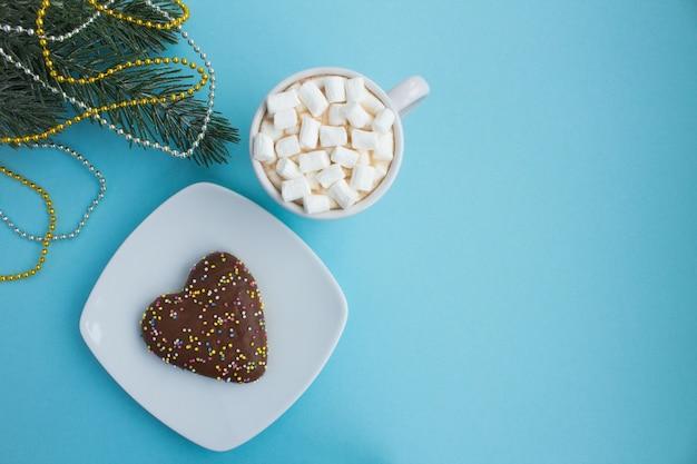 Heiße schokolade mit marshmallows in der weißen tasse und weihnachtskomposition auf blau