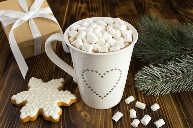 Heiße schokolade mit marshmallows in der weißen tasse und weihnachtskomposition auf dem braunen holz