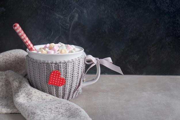Heiße schokolade mit marshmallows, rotes herz auf der tasse auf dem tisch
