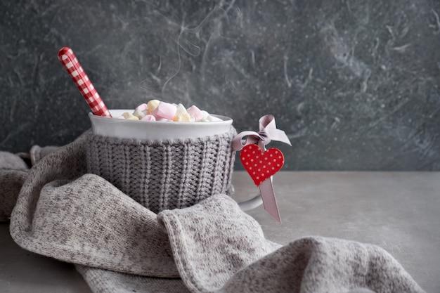 Heiße schokolade mit marshmallows, rotes herz auf der tasse, kopierraum